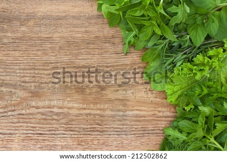 Fresh green herbs on old wooden background - stock photo
