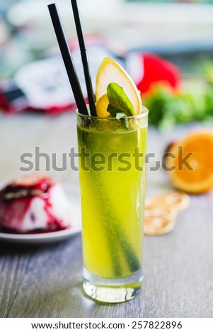 fresh green kiwi soft lemonade in a glass on a wooden table with decorations focus on different parts of the glass - stock photo