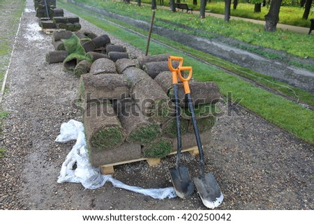 Fresh green lawn in rolls and two spades - stock photo