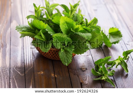 Fresh green leaves of melissa and peppermint in bowl on wooden background. Selective focus, horizontal. - stock photo