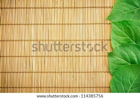 Fresh Green Leaves on Bamboo Mat - stock photo