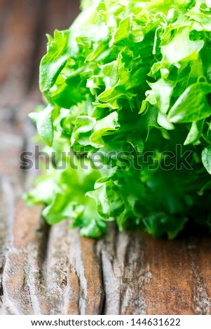 Fresh green lettuce on wooden table - stock photo