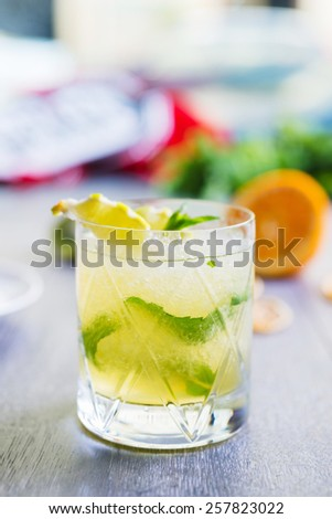 fresh green lime soft lemonade in a glass on a wooden table with decorations focus on different parts of the glass - stock photo