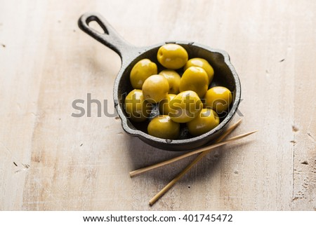 Fresh green olives in miniature iron pan with toothpick on a wood table - stock photo