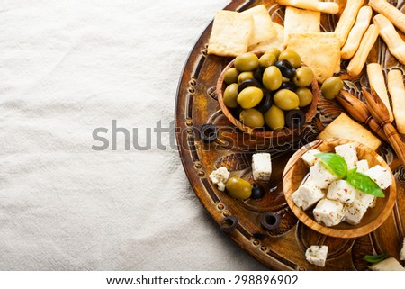 Fresh green olives in olive wood bowl and feta cheese on rustic wooden background.  Selective focus. Food background with copy space. - stock photo