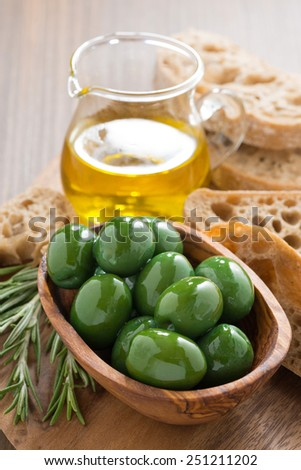 fresh green olives, olive oil and ciabatta, close-up - stock photo