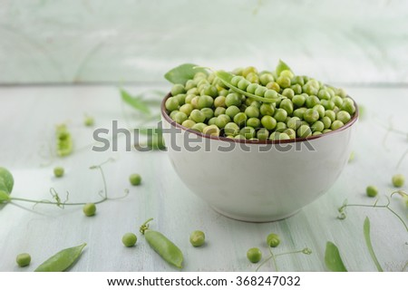 Fresh green peas in a ceramic bowl on the wooden table - stock photo