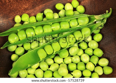 Fresh green peas in a wooden bowl.
