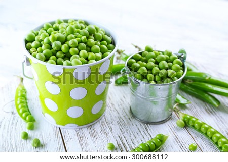 Fresh green peas in metal buckets on white wooden table, closeup - stock photo