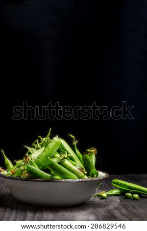 fresh green peas in rustic iron bowl on a dark textured backgroud - stock photo