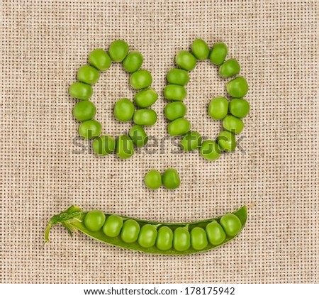 Fresh green peas laid out in the form of a mug on a sacking - stock photo