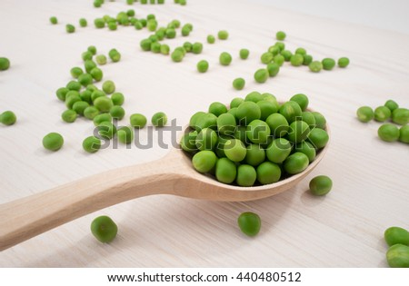 fresh green peas on a white table - stock photo