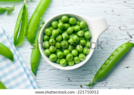 fresh green peas on old cracked table - stock photo