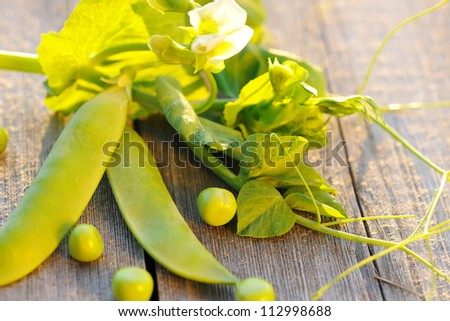 Fresh green peas pods on a wooden table