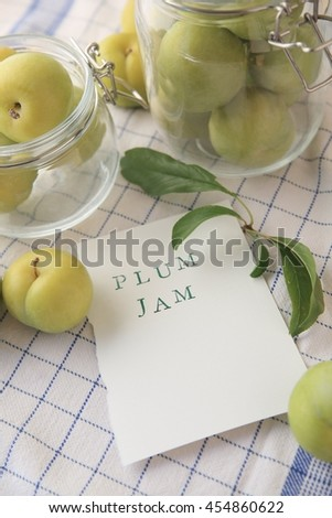 Fresh green plums in glass jars and the words plum jam on paper with copy space - stock photo