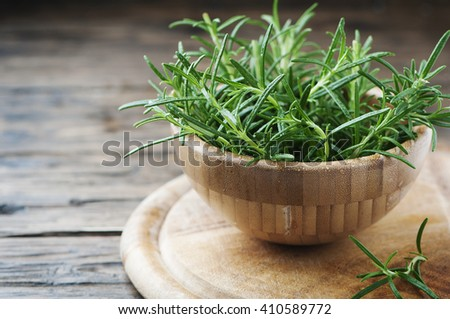 Fresh green rosemary on the wooden table, selective focus