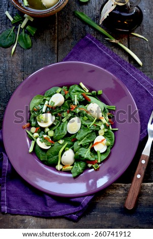 Fresh green salad with baby spinach, wild garlic and marinated quail eggs - stock photo