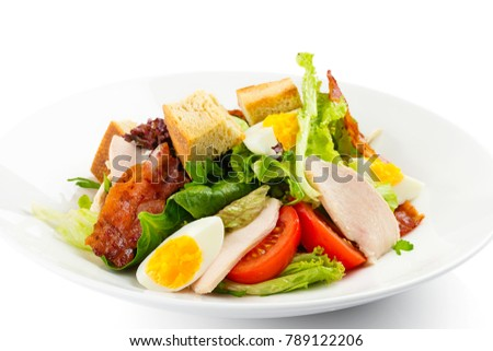 Fresh green salad with chicken, bacon, eggs, tomatoes and croutons in white plate isolated on white. Restaurant menu or recipe illustration with copy space