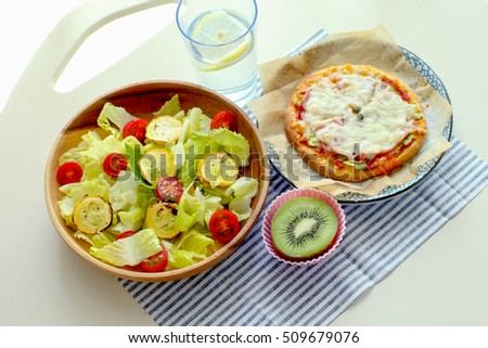 fresh green salad with kiwi fruit and pizza