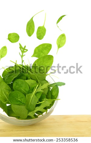 Fresh green salad with some leaves flying out of a bowl isolated - stock photo