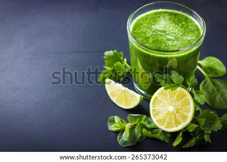 fresh green smoothie with ingredients on dark background - stock photo