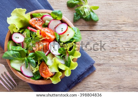 Fresh green spring vegetable salad with cucumber, radish, tomatoes and seeds in wooden bowl over rustic background with copy space - stock photo