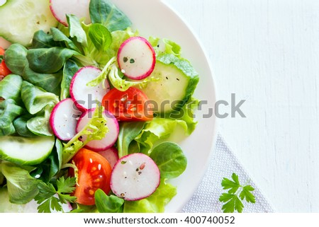 Fresh green spring vegetable salad with cucumber, radish, tomatoes and seeds  over white wooden background with copy space - stock photo