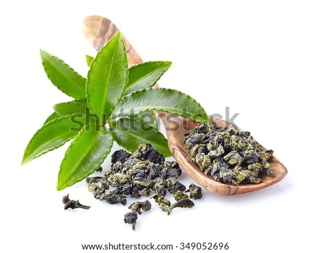 Fresh green tea leaves with wooden spoon