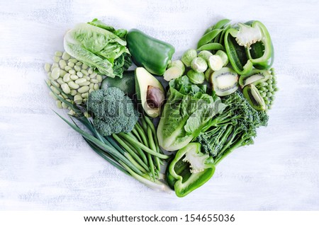 Fresh green vegetables arranged in a heart shape on white rustic background, broccoli, broad beans, capsicum, kiwi, avocado, beans, peas, peppers for healthy living concept  - stock photo