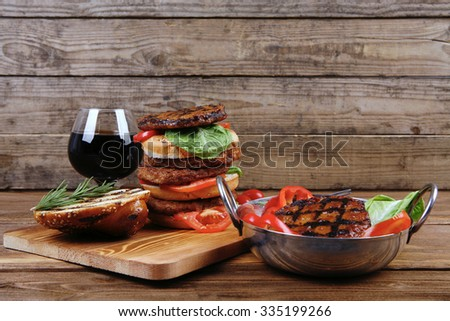 fresh grilled beef double huge hamburger served on wooden plate with wine cherry tomatoes and rosemary over table - stock photo