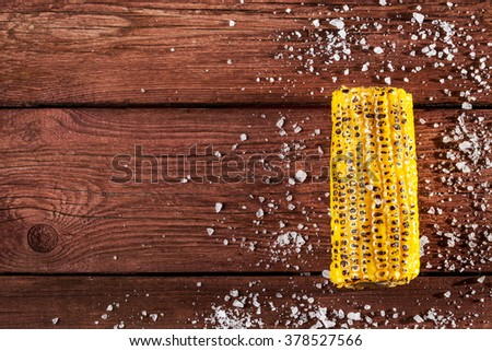 Fresh grilled corn cob with salt on wooden table, copy space, top view - stock photo