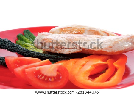 fresh grilled turkey meat fillet steak on red plate with tomatoes pepper green kale and lettuce salad isolated over white background - stock photo
