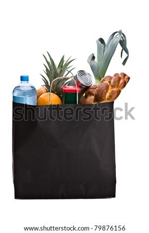 Fresh groceries in a brown bag. Including bread, orange, water, can and leek - stock photo