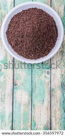 Fresh ground coffee in white bowl over wooden background