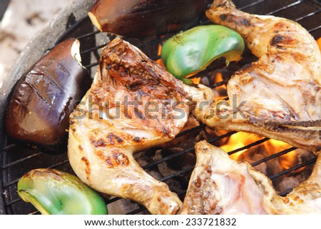 fresh group of grilled chicken thighs with green orange yellow pepper bell slice and eggplants on hot grill bbq - stock photo