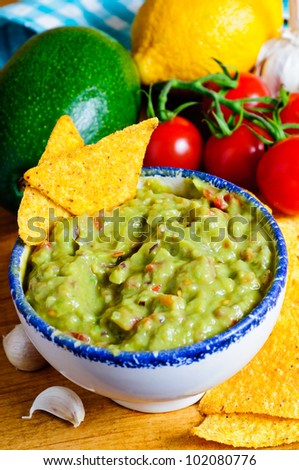 Fresh guacamole dip with avocado, ingredients and nacho chips - stock photo