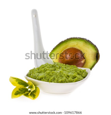 Fresh guacamole in a white bowl with a spoon isolated on white background - stock photo