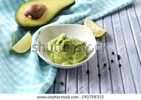 Fresh guacamole in bowl on wooden table