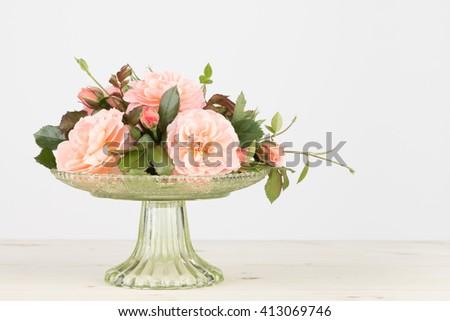 Fresh gut pink garden roses arranged in a glass pedestal vase, in horizontal format. - stock photo