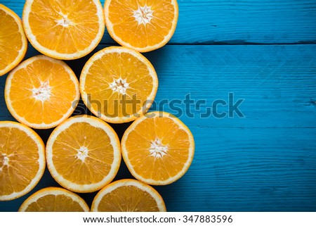 Fresh half cut oranges on wooden blue table - stock photo
