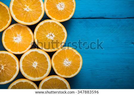 Fresh half cut oranges on wooden blue table - stock photo