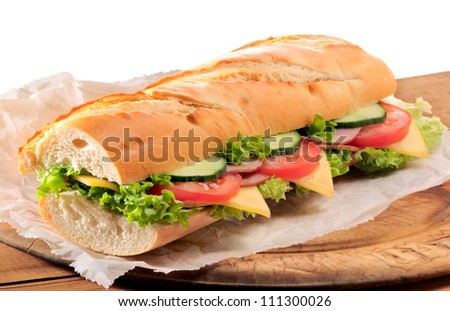 Fresh ham and cheese salad submarine sandwich on old wooden cutting board with isolated white background - stock photo