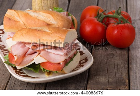Fresh ham and cheese sandwich with lettuce and tomato on a baguette