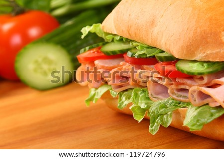 Fresh ham sandwich on wooden board - close up - stock photo