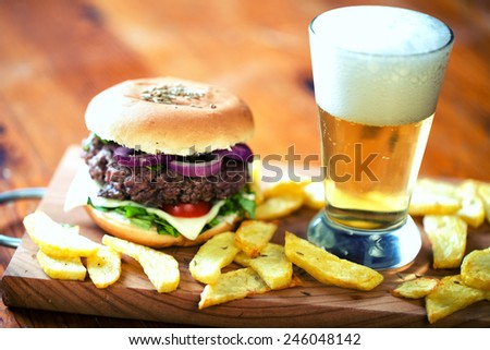 Fresh hamburger with beer and fried potatoes - stock photo