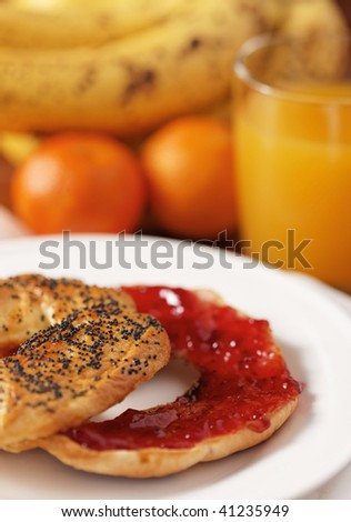 fresh handmade bagel for the breakfast with fruit and juice in the background. Very shallow depth of field. - stock photo