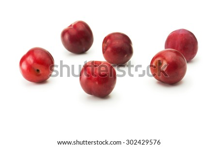 Fresh harvested red ripe plums, isolated on white. Five shiny red plums on white surface. - stock photo