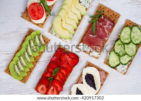 Fresh healthy appetizer snack with crispbread, fruits, berries, hamon and cheese
