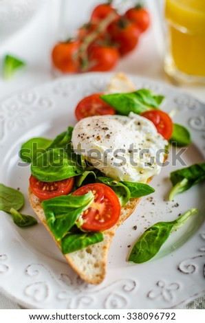 Fresh Healthy Breakfast - poached egg on baguette with salad, tomato and olive oil, very simple and delicious, place for your advertisment - stock photo