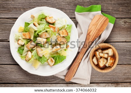 Fresh healthy caesar salad with chiken on wooden table. Top view - stock photo